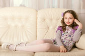 Fashion little girl lying on sofa — Stock Photo