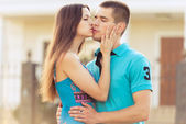 Woman kisses boyfriend on street — Stock Photo