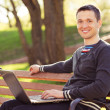 Royalty-Free Stock Photo: Man with computer sitting bench in park