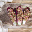Boat of brown rice with red radicchio and speck — Stock Photo