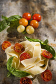 Nest of pasta with basil and tomato  — Stock Photo