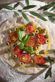 Raw pizza with tomato and olives  — Stock Photo