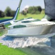 Yacht golf concept metaphor.Yacht hit by a golf club. Kick off. — Stock Photo
