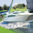 Stock Photo: Yacht golf concept metaphor.Yacht hit by golf club. Kick off.