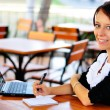 Businesswoman with a cute smile with laptop and notepad — Stock Photo #14148038