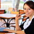 Smiley woman with laptop holding a pen in the hand — Stock Photo