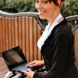 Stock Photo: Businesswoman on a bench at the street using laptop