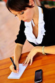 Woman writing to the notepad — Stock Photo
