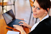 Businesswoman with laptop turned to look at the camera — Stock Photo