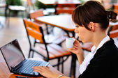 Female with a cup of coffee using laptop — Stock Photo
