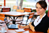 Businesswoman with a cute smile with laptop and notepad — Stock Photo