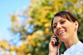 Smiley woman talks on mobile phone with copy-space — Stock Photo