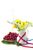 Still life of cherries and flowers in a vase on a white background — Stock Photo