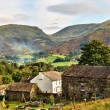 Traditional Farmhouse and Lakeland fells - Stock Photo