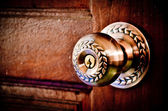 Color photo of a metal handle on a wooden door — Stock Photo