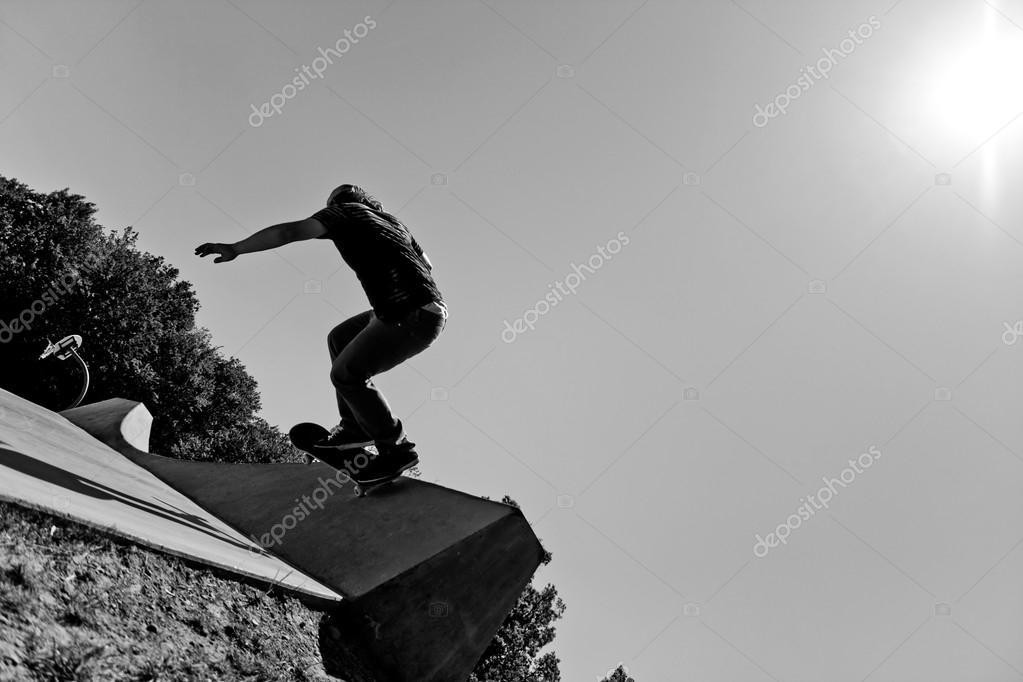 Silhouette of a young skateboarder doing a wall ride trick at the top of the ramp at a concrete skate park. Black and white with high contrast.. — Stock Photo #13111221