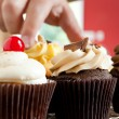 Hand Grabbing Gourmet Cupcake — Stock Photo #23369914