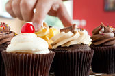 Main saisissant un cupcake gourmet — Photo