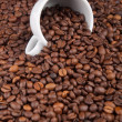 A white cup with many coffee beans on coffe background - Stock fotografie