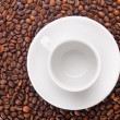 A white cup on beans background - Stock Photo