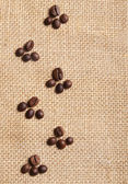 Trace of coffee beans on burlap background — Stock Photo