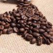 Stock Photo: White cup with coffee beans on burlap background.