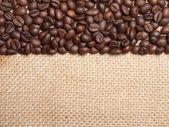 Coffee beans on burlap background — Stock Photo