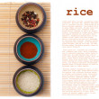 Ceramic bowls with spices and rice on bamboo placemat with sampl — Stock Photo
