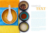 Ceramic bowls with spices and rice on color placemat with sample — Stock Photo