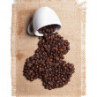 White cup with coffee beans on burlap background. - Stock Photo