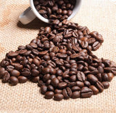 コーヒー豆の黄麻布の背景と白いカップ. — ストック写真