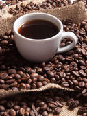 White cup with coffee on burlap background with beans — Stock Photo