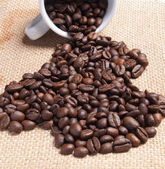 White cup with coffee beans on burlap background. — Stock Photo
