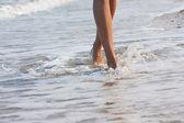 Woman walking on the sand beach — Stock Photo