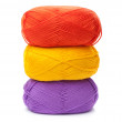 Stack of yarn skeins in red, yellow, purple colors on white back — Stock Photo