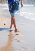 Woman walking on the sand beach — Stok fotoğraf