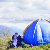 男子躺在睡袋帐篷旁 — 图库照片