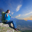Stock Photo: Womwith backpack enjoying sunset on top of mountain