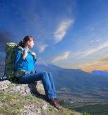 žena s batohem, užívat slunce na vrcholu hory — Stock fotografie