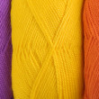 Stock Photo: Background of yarn skeins in yellow, orange and purple colors