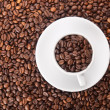 Stock Photo: White cup with many coffee beans on coffe background