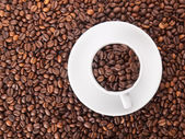 A white cup with many coffee beans on coffe background — Stock Photo