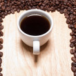 Stock Photo: Cup of coffe on breadboard with coffee grains