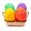 Stock Photo: Four yarn skeins in yellow, orange, green, purple colors in bask
