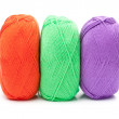 Stock Photo: Stack of yarn skeins in red, green, purple colors on white backg