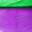 Stock Photo: Background of yarn skeins in green, purple and white colors