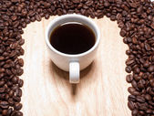 A cup of coffe on breadboard with coffee grains — Stock Photo