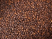 Numerous coffee beans which have been scattered all over the sur — Stock Photo
