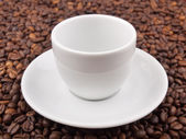 White cup on coffee beans — Stock Photo