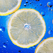 Lemon with water drops on blue background. Bubbles, mineral water, glass. — Stock Photo